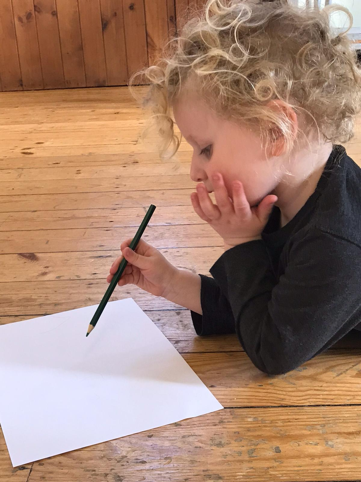 A toddler focussed on drawing.