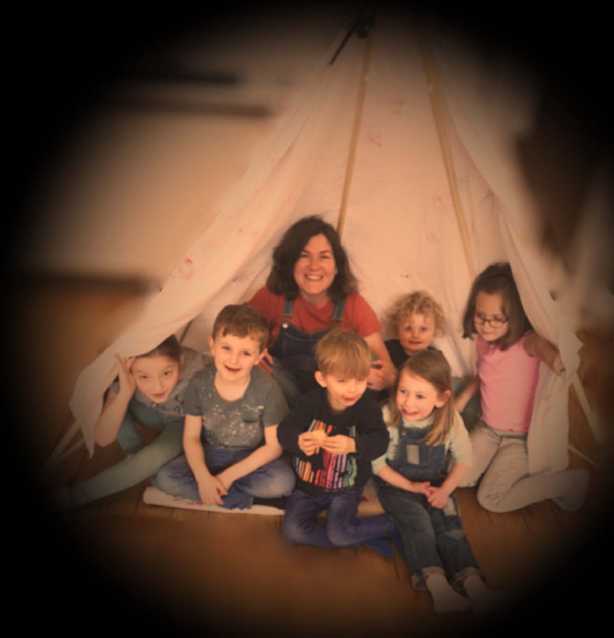 Beccy and story-trails children sitting in a teepee and smiling.